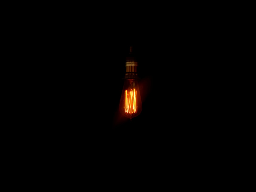 turned-on yellow incandescent bulb