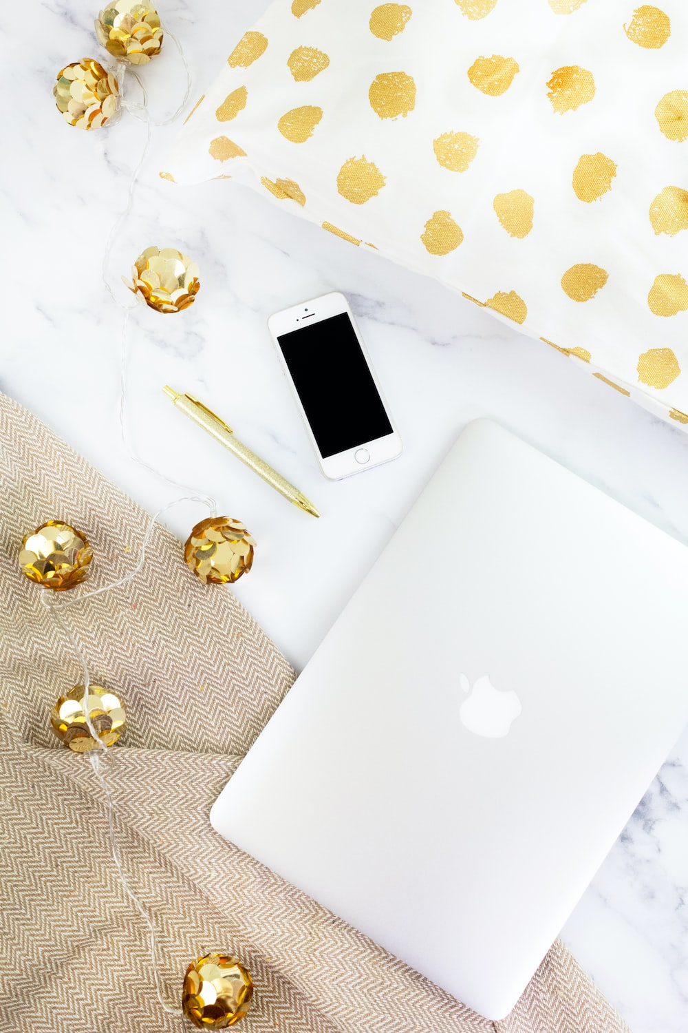 gold iPhone beside pen on white textile