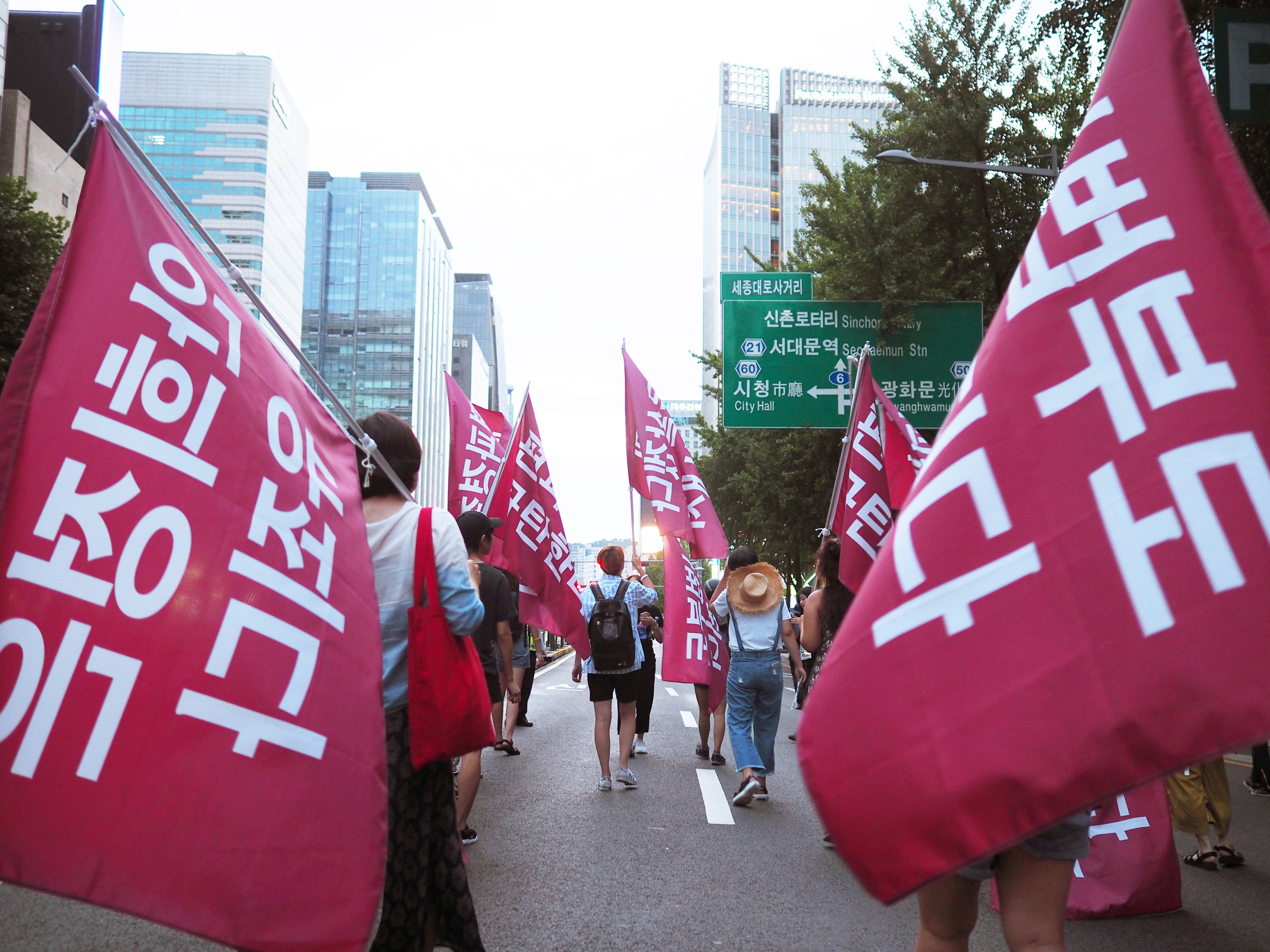 people on road with banners during daytime