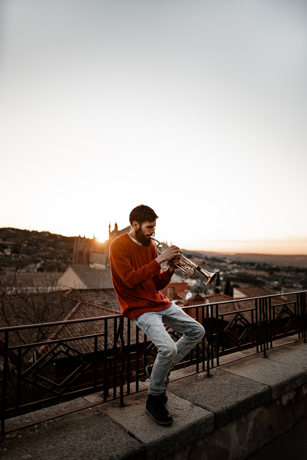man sitting on railing while playing wind instrument outdoors during daytime