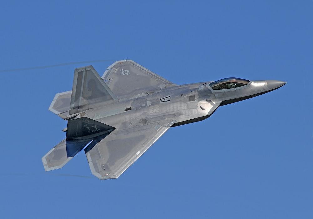 flying gray jet plane