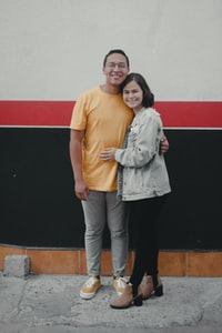 man and woman standing in front of white and black wall