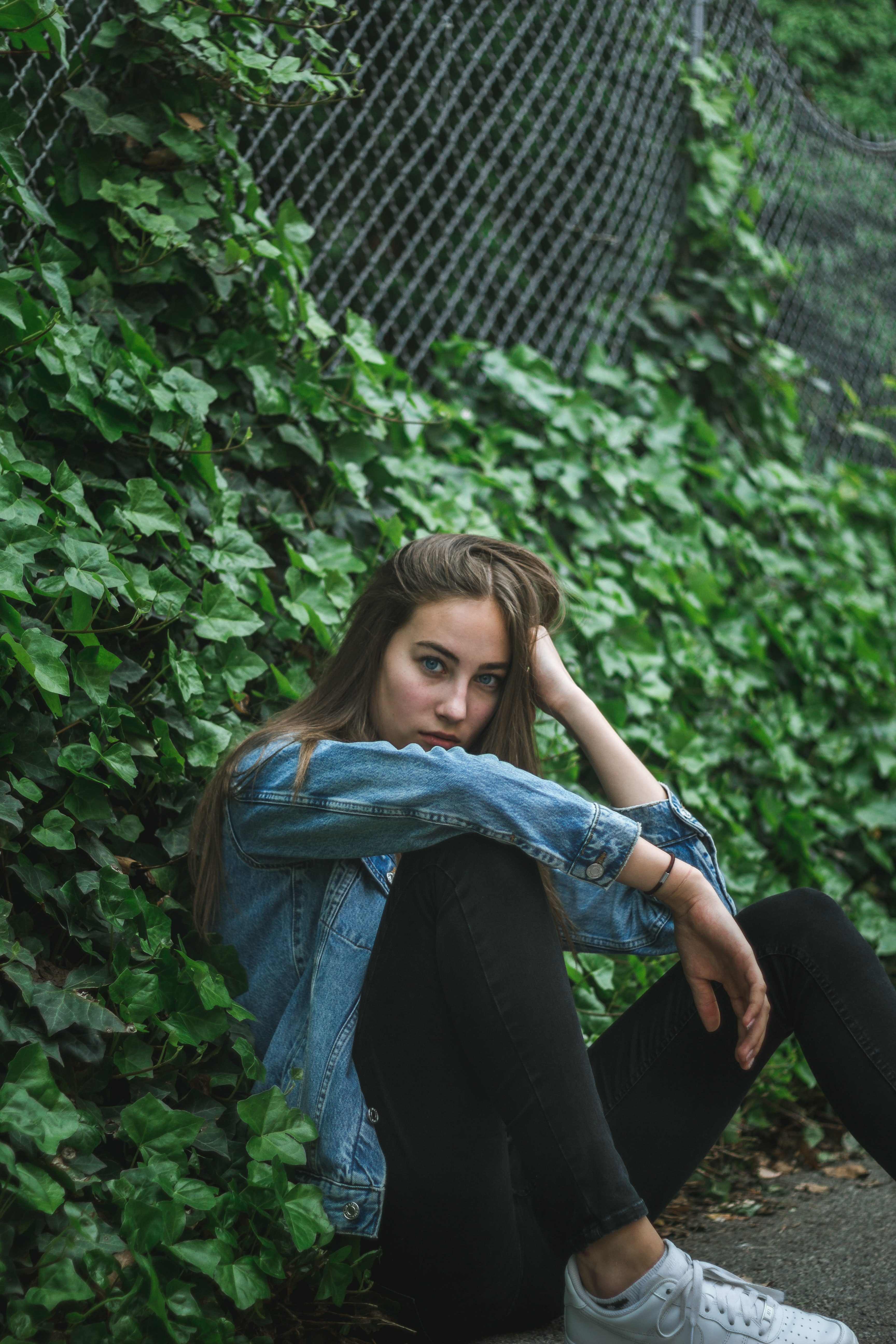 woman sitting against wire fence with crawling vine plants