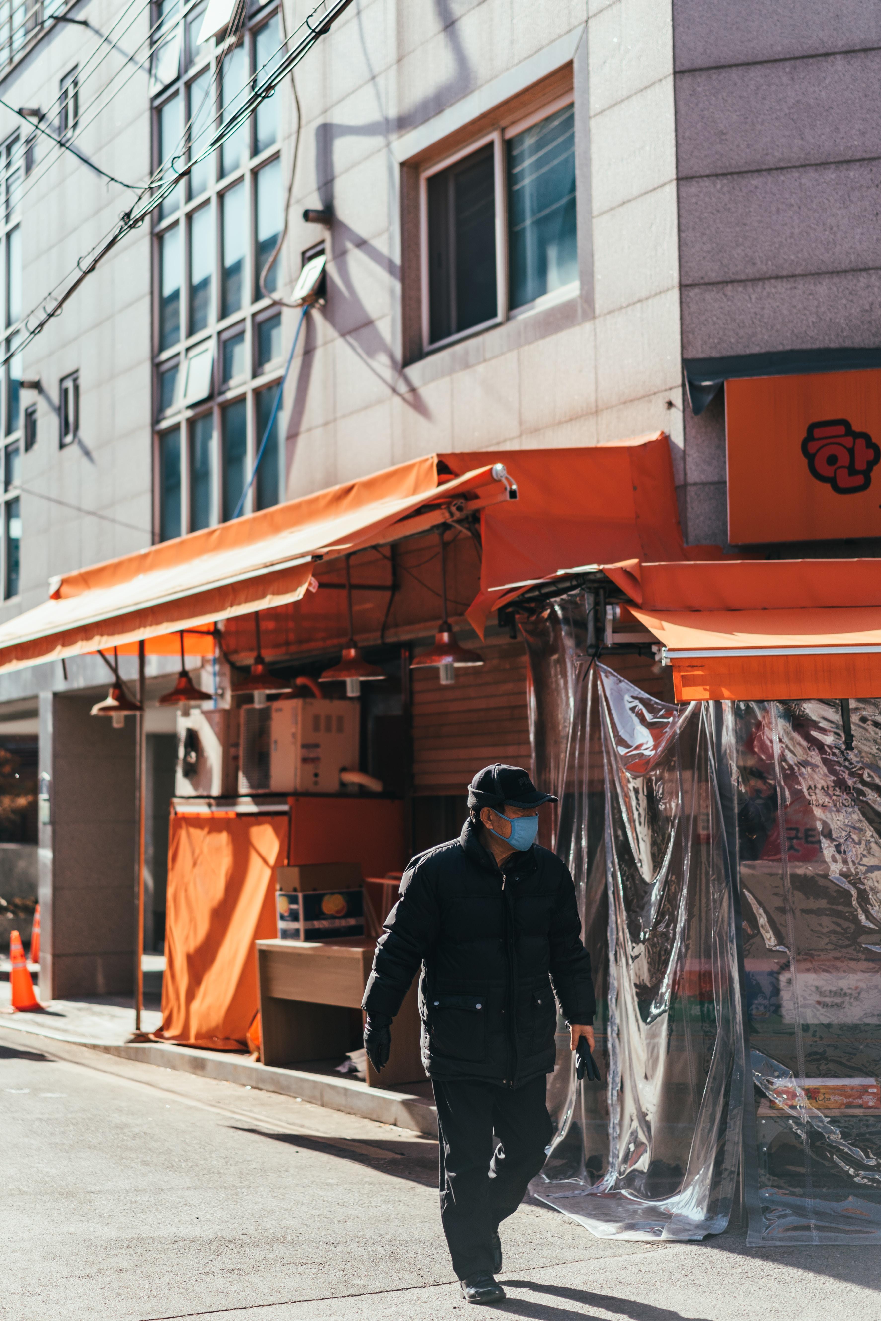 man walking on street beside store during daytime