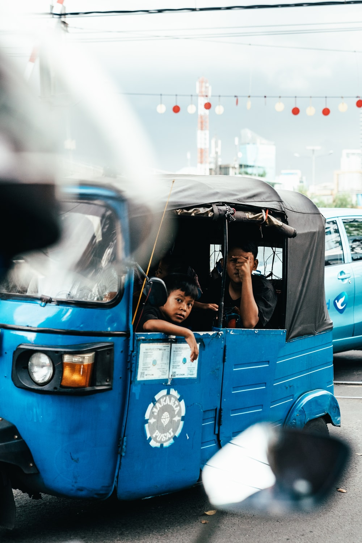 people riding autorickshaw during day