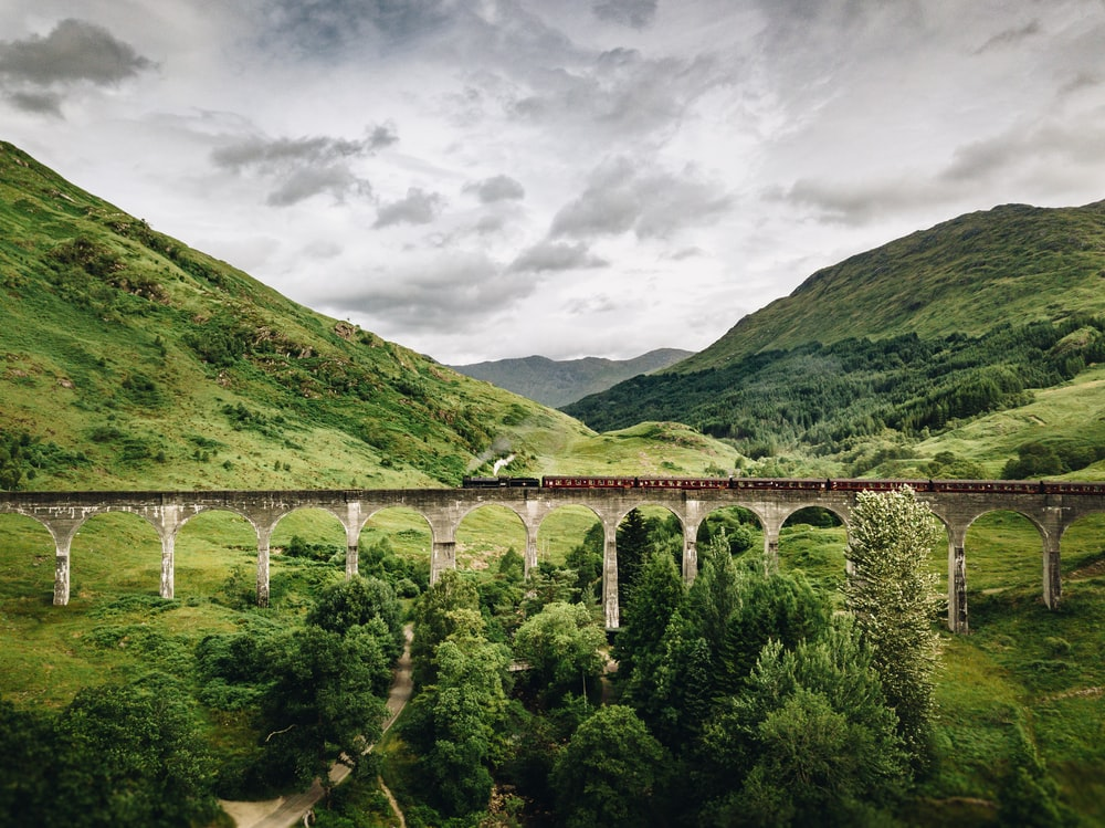 train passing by bridge over mountains