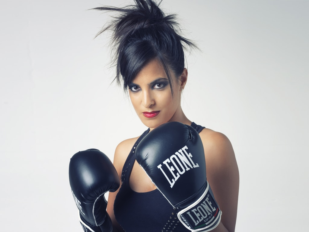 boxer woman wearing black Leone leather boxing gloves
