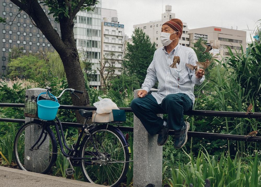 man sitting beside black commuter bike