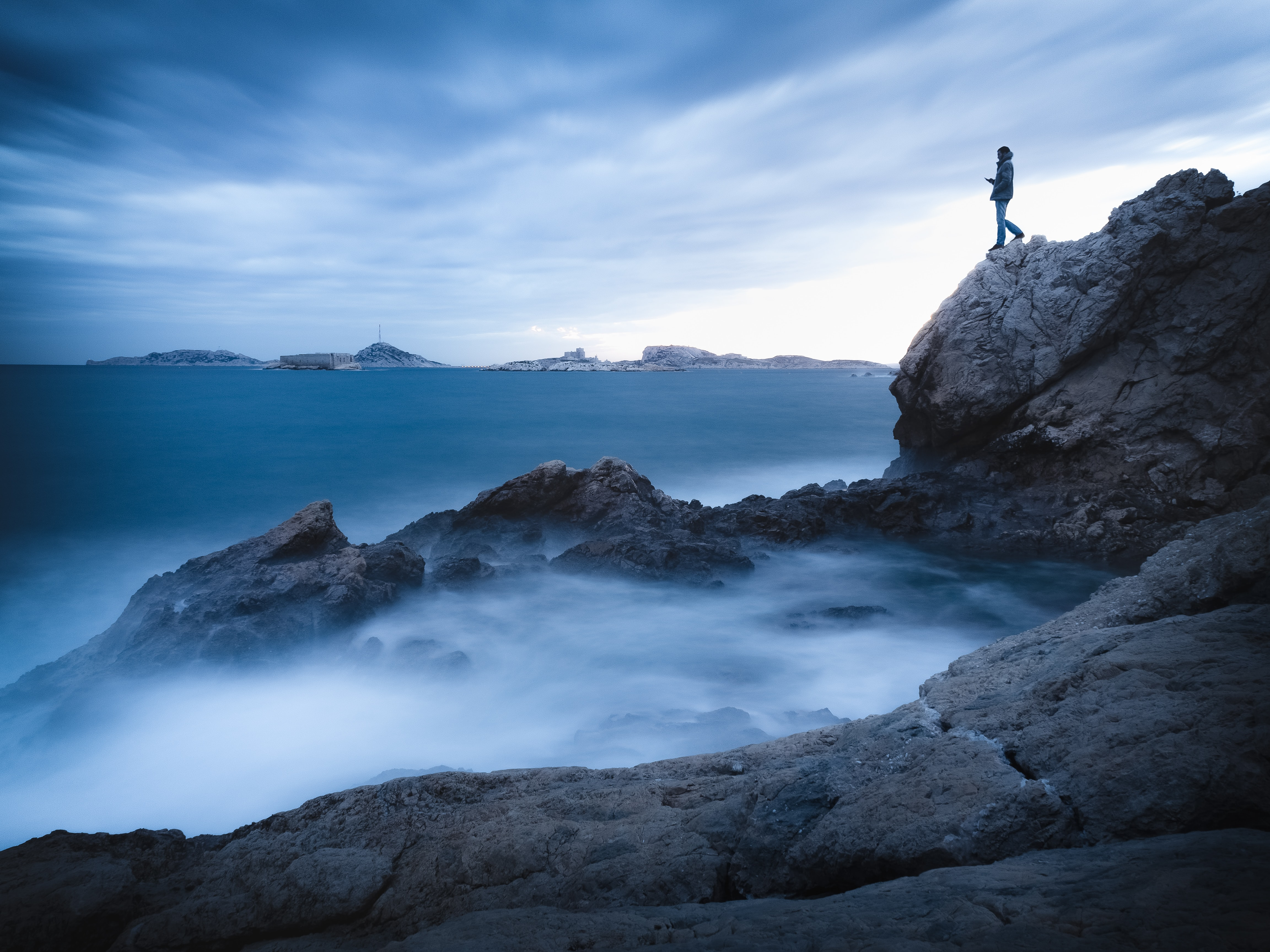 man standing on mountain cliff by the sea