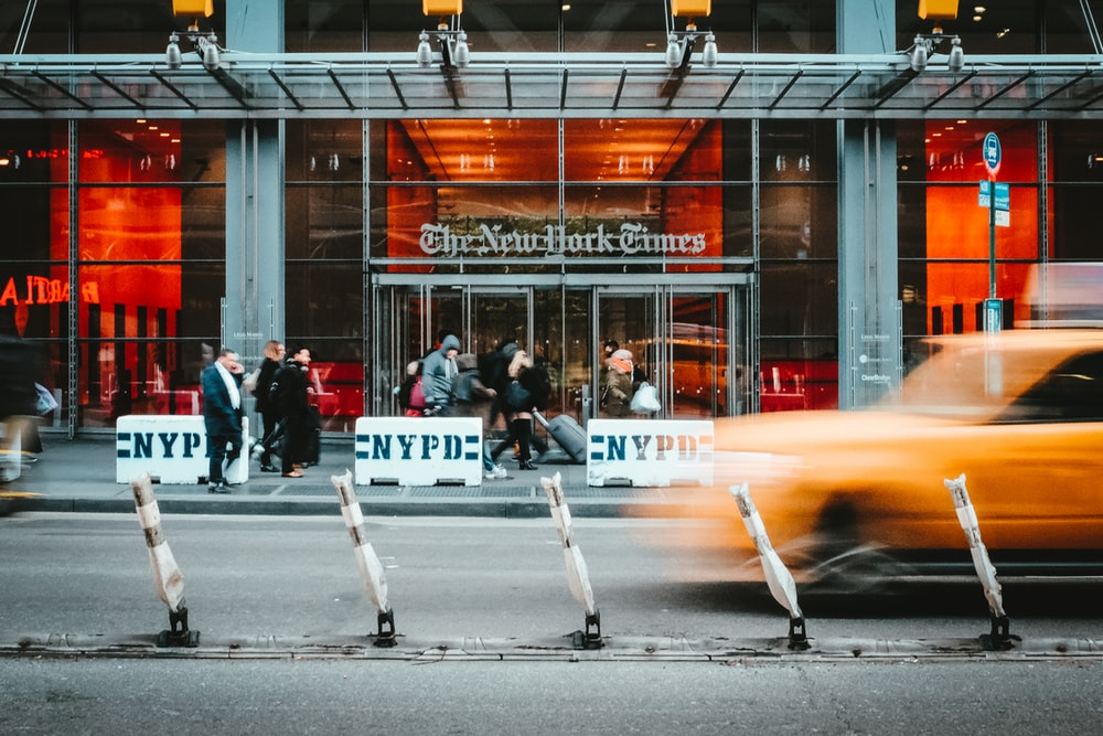 time lapse photo of yellow taxi driving past the NYT