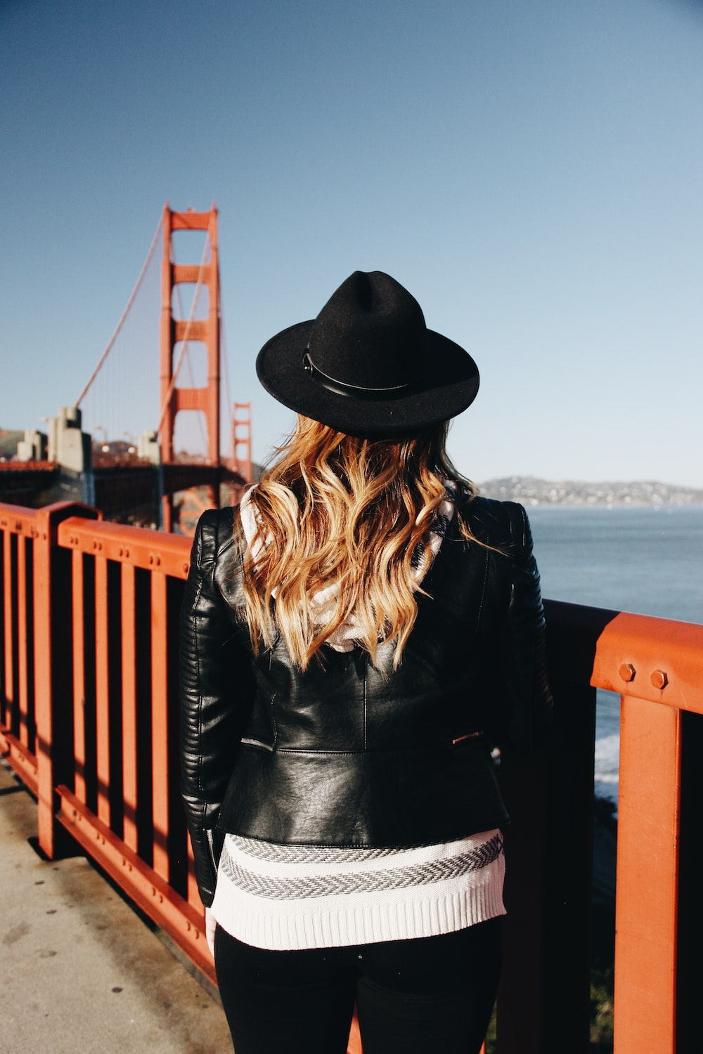 woman wearing black leather jacket and hat while facing red bridge during daytime