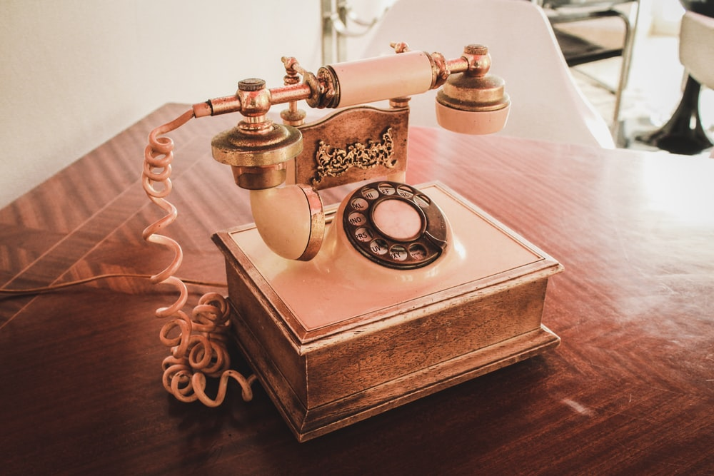 white and brown rotary telephone on brown wooden table