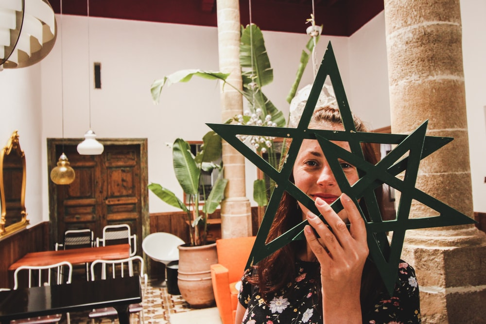 woman holding two star decors in front of her face