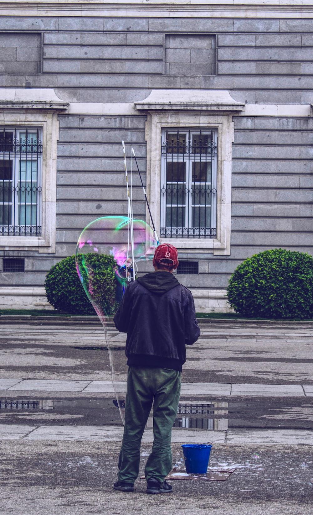 man forming giant bubble outside house