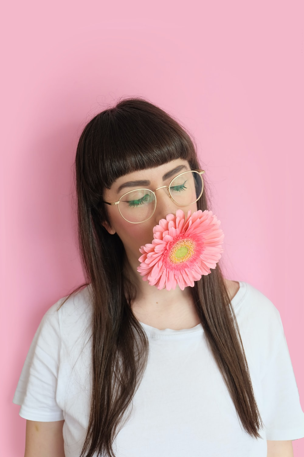woman wearing eyeglasses with flower in mouth