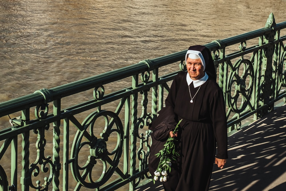 nun walking near the ocean
