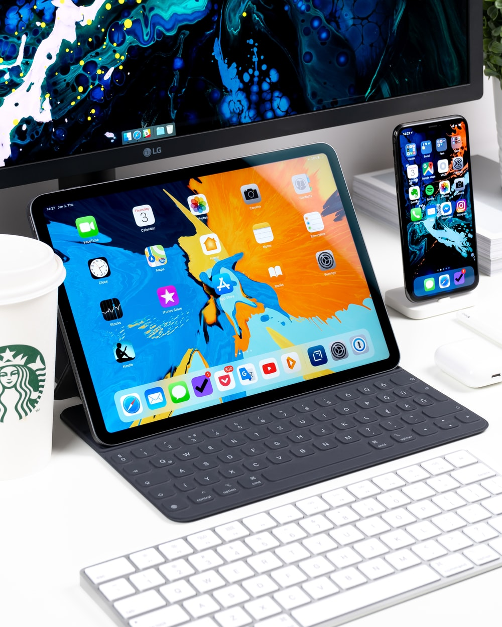 black iPad near the white keyboard