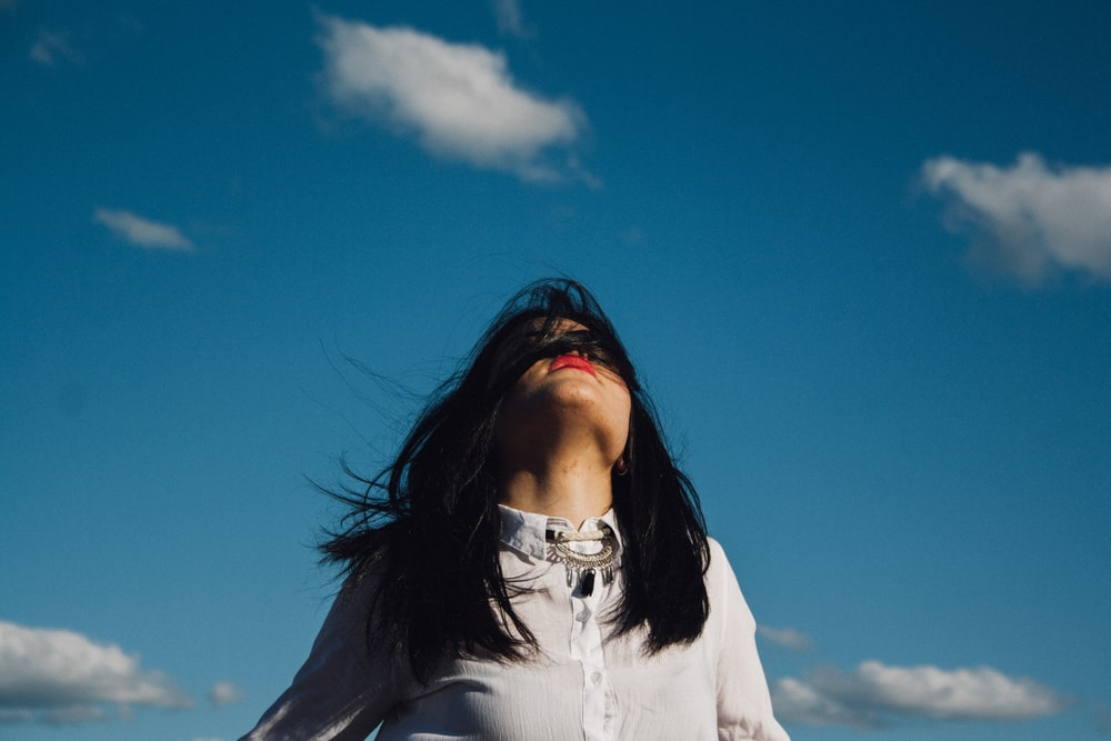 woman wearing white button-up top under blue sky
