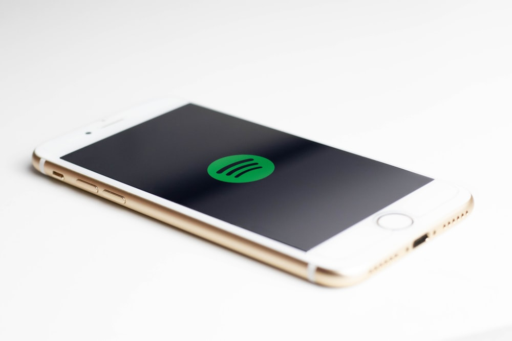 gold iPhone 7 displaying spotify logo