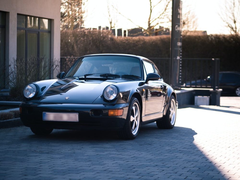 black Porsche 911 parked in front of house