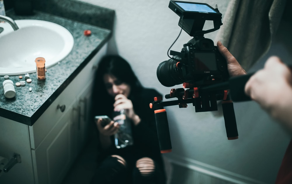 person taking video of woman sitting on wall in front of sink with cabinet