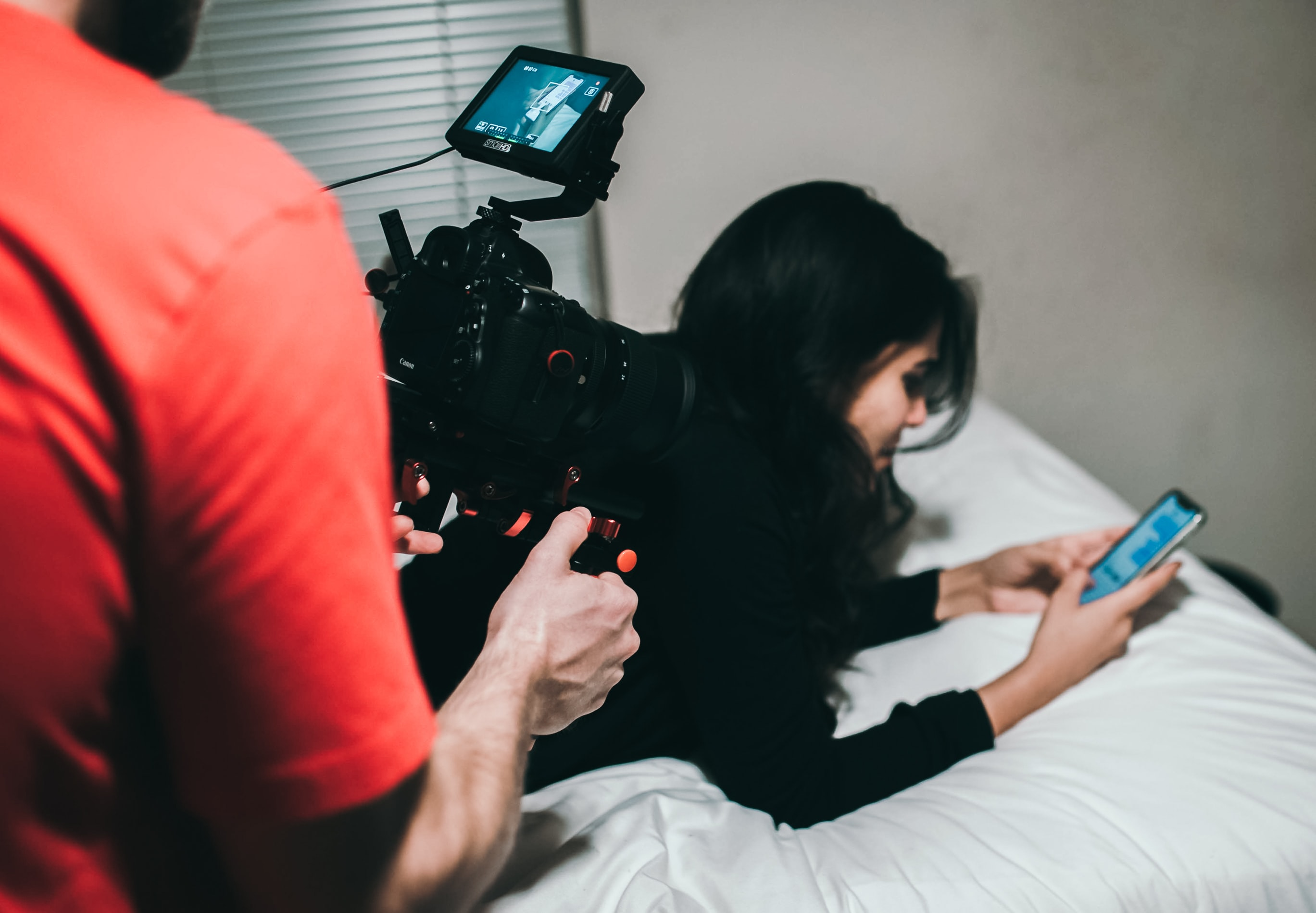 woman holding smartphone while lying on bed near man holding professional camera