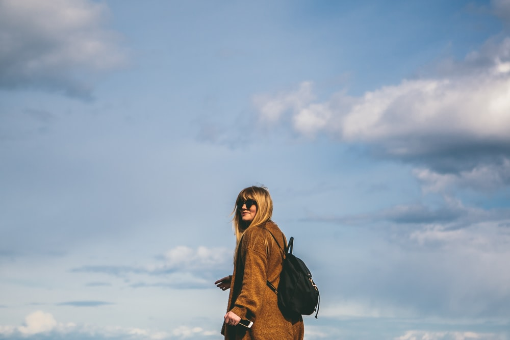 woman wearing brown coat with black backpack