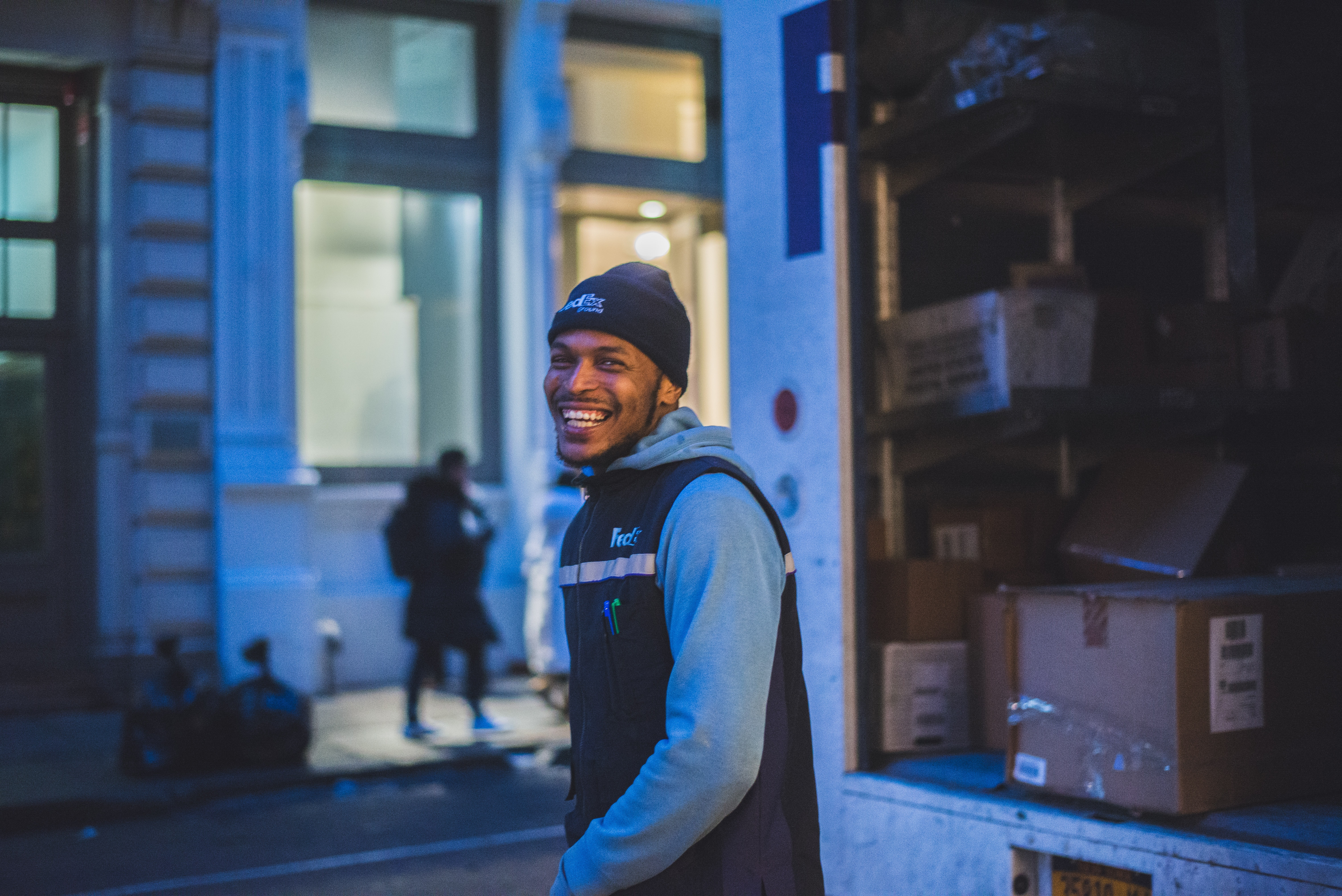 Delivery smiling man stands behind delivery truck