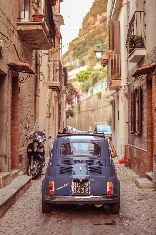 blue Volkswagen Beetle on narrow pathway between houses
