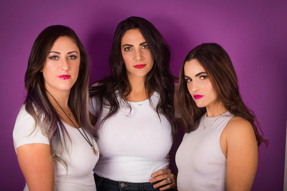 three women wearing white shirt