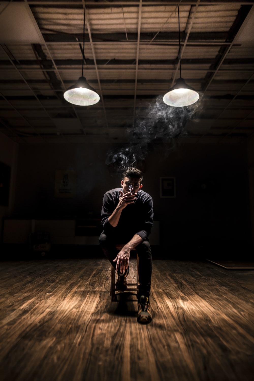 man sitting on chair while smoking