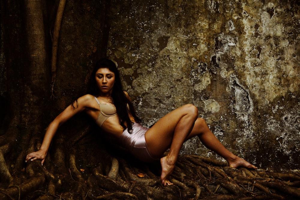 woman beside brown concrete wall