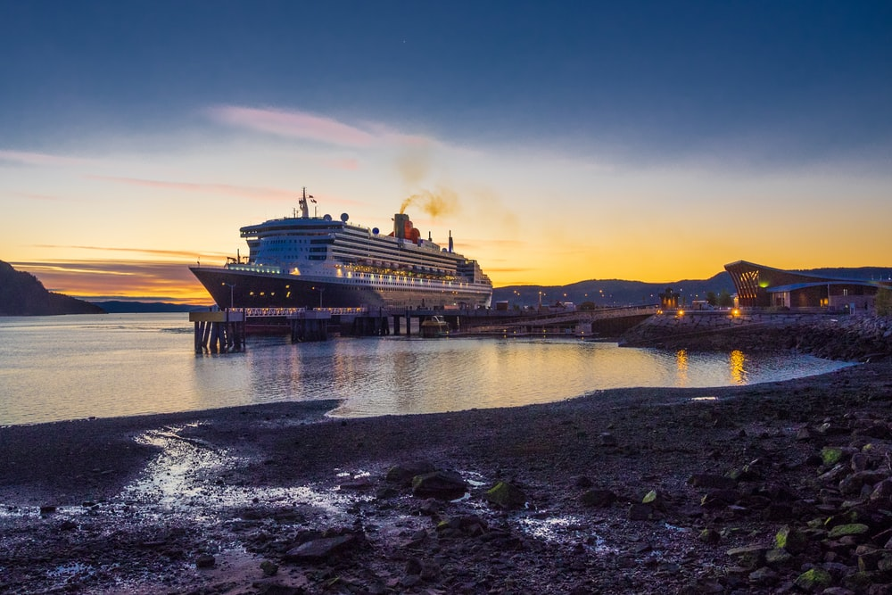 ship on dock under blue and red sky during sunset