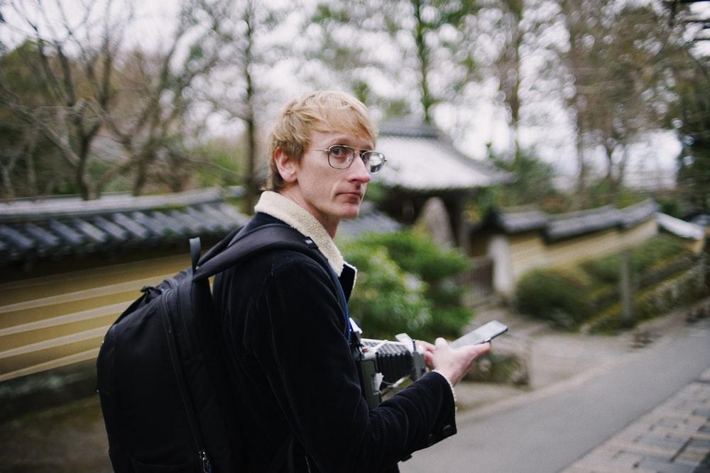 man wearing black backpack holding black smartphone