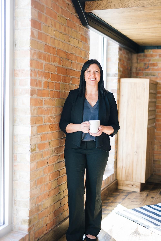 woman standing by wall holding mug