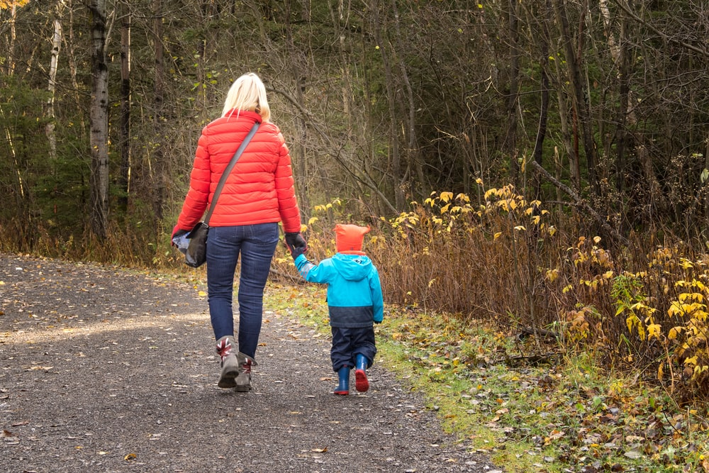 woman and boy walking on road near bush during daytime