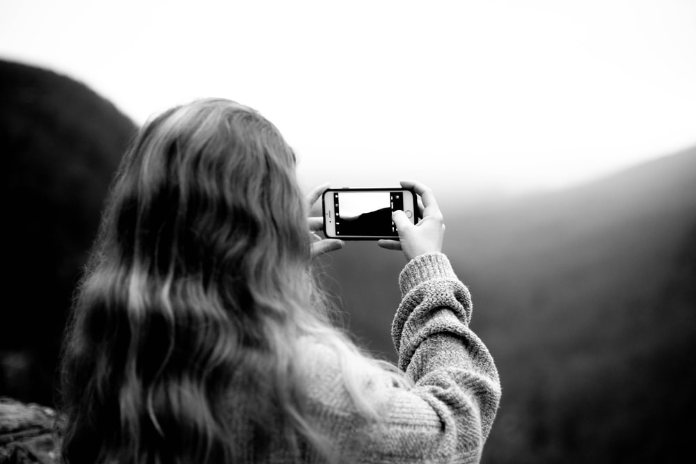 grayscale photography of woman wearing sweater using smartphone taking picture