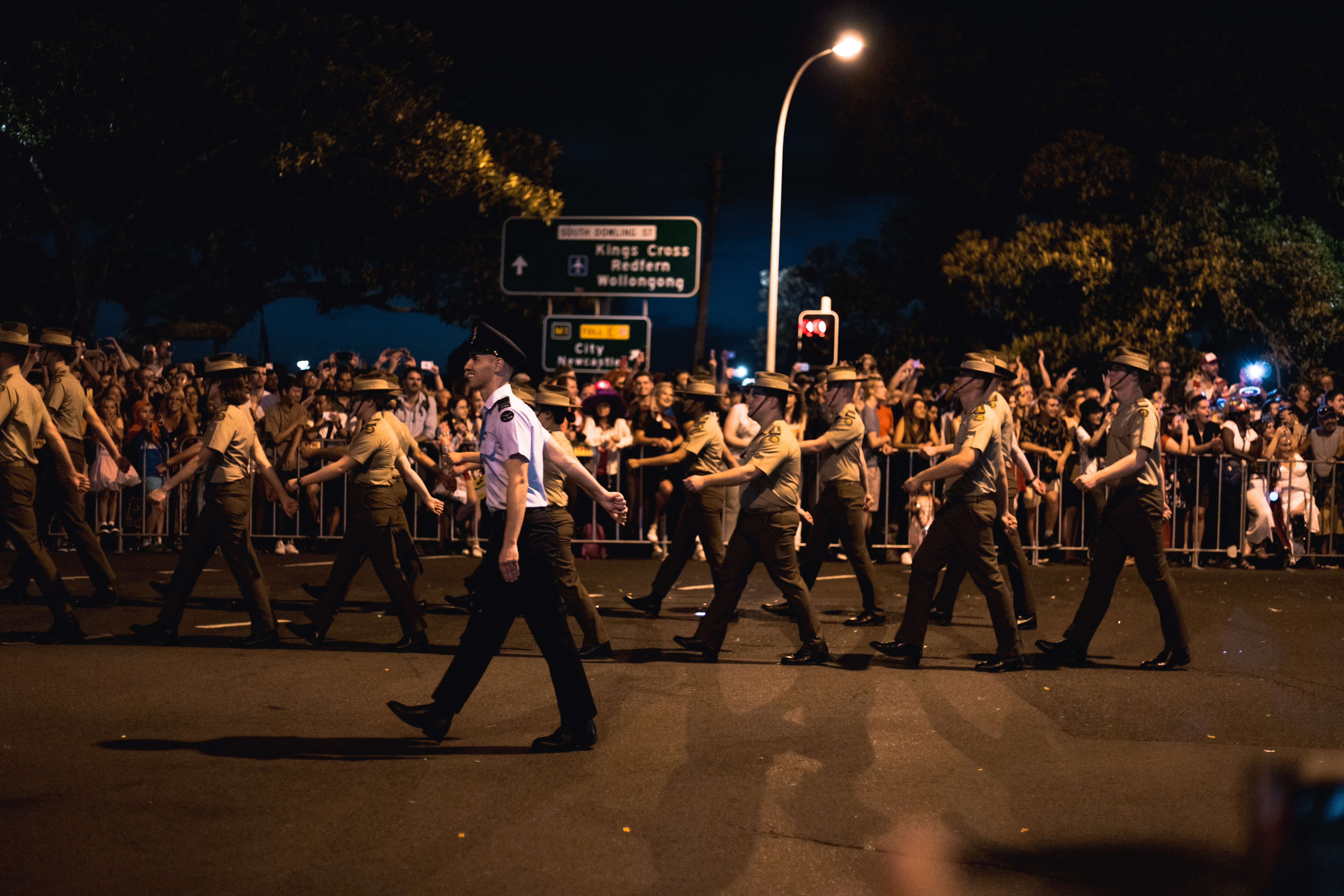 group of police officials marching on road at night with people watching