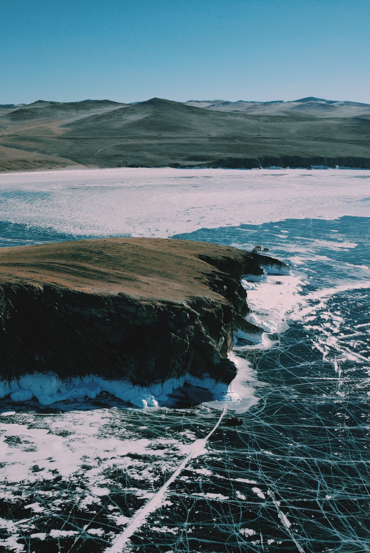 sea waves splashing through rocks near rock formation