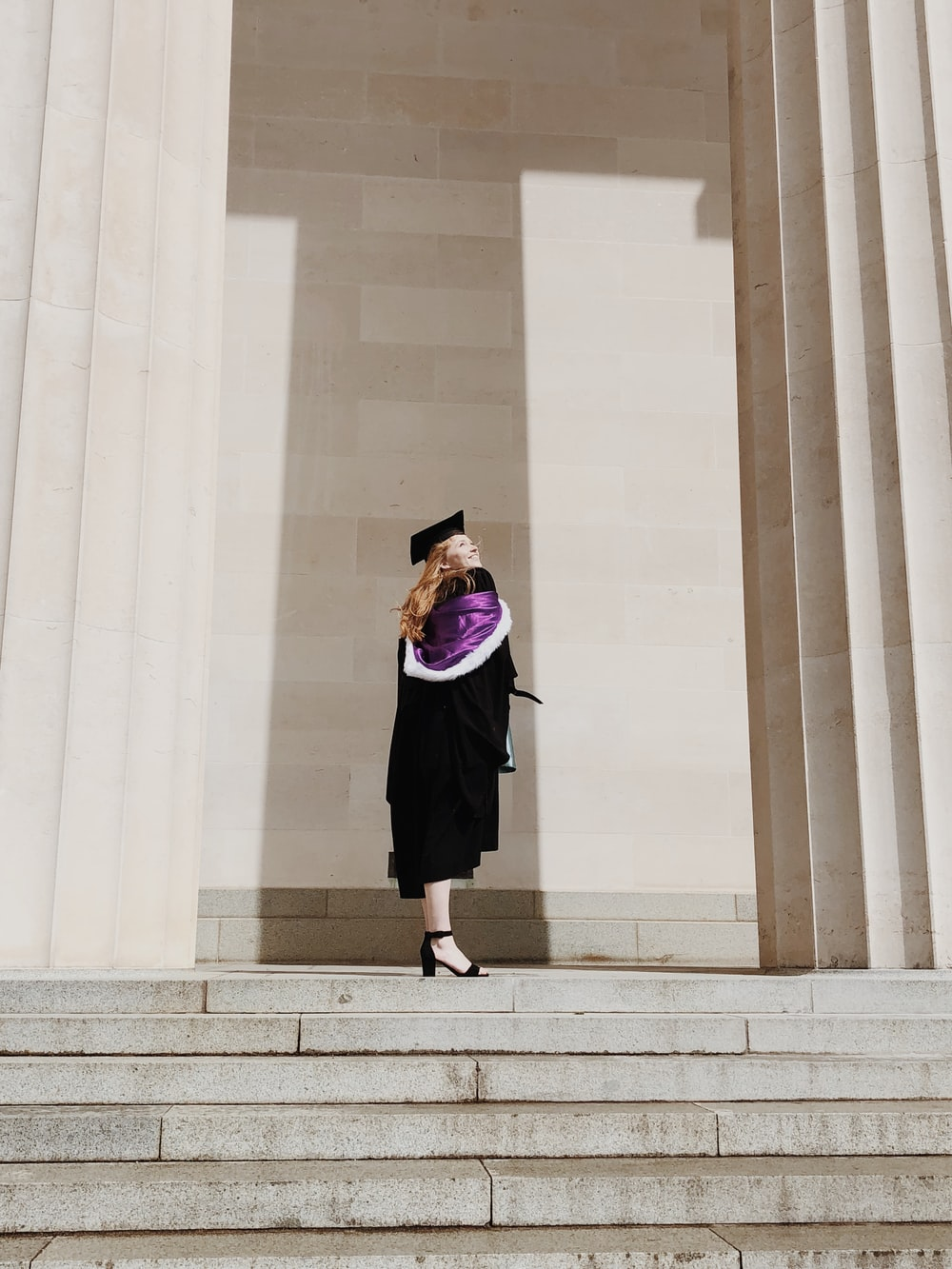 woman in academic regalia standing near concrete stairs