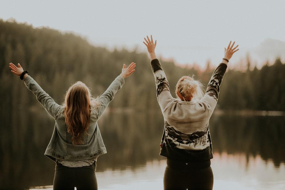 two women hands up standing beside body of water