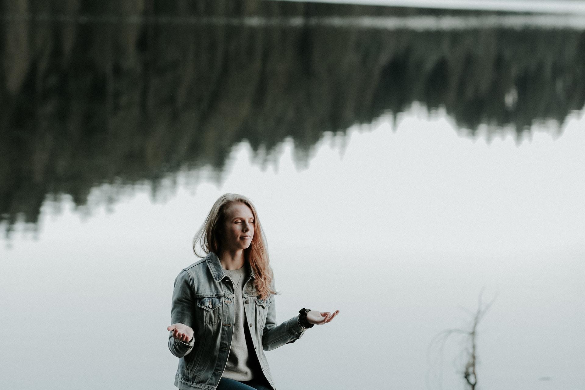 woman meditating on rock in bank of lake