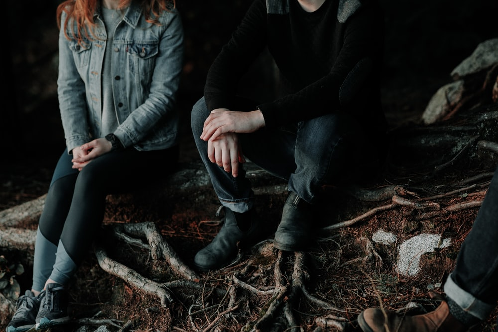 two person sitting on wood slab