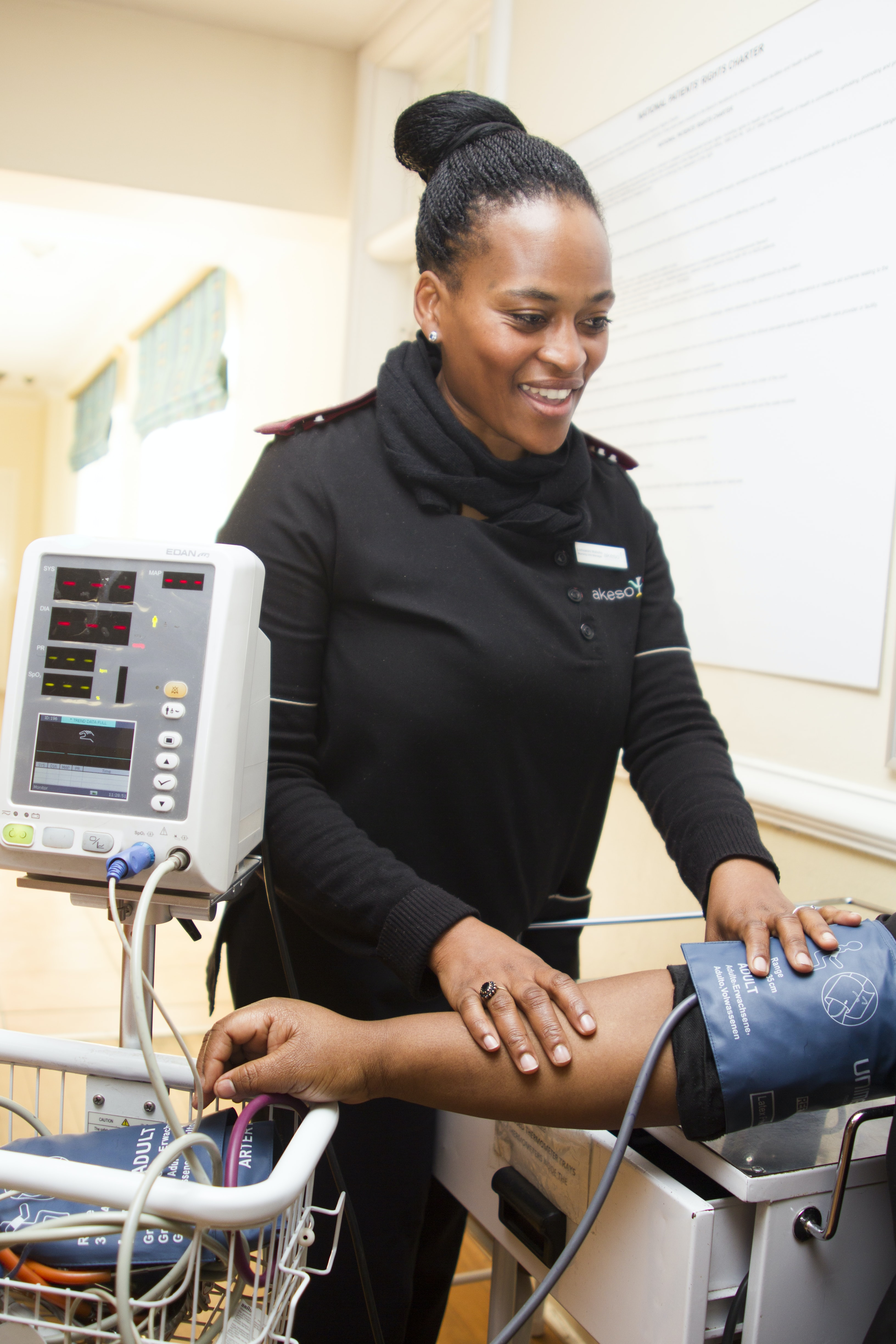 woman aiding a person using blood pressure monitor
