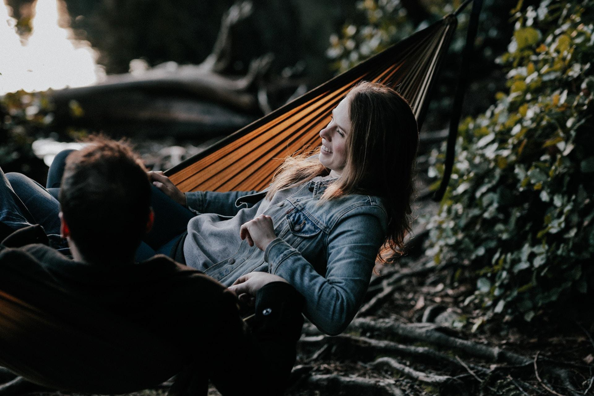 man and woman lying on hammock