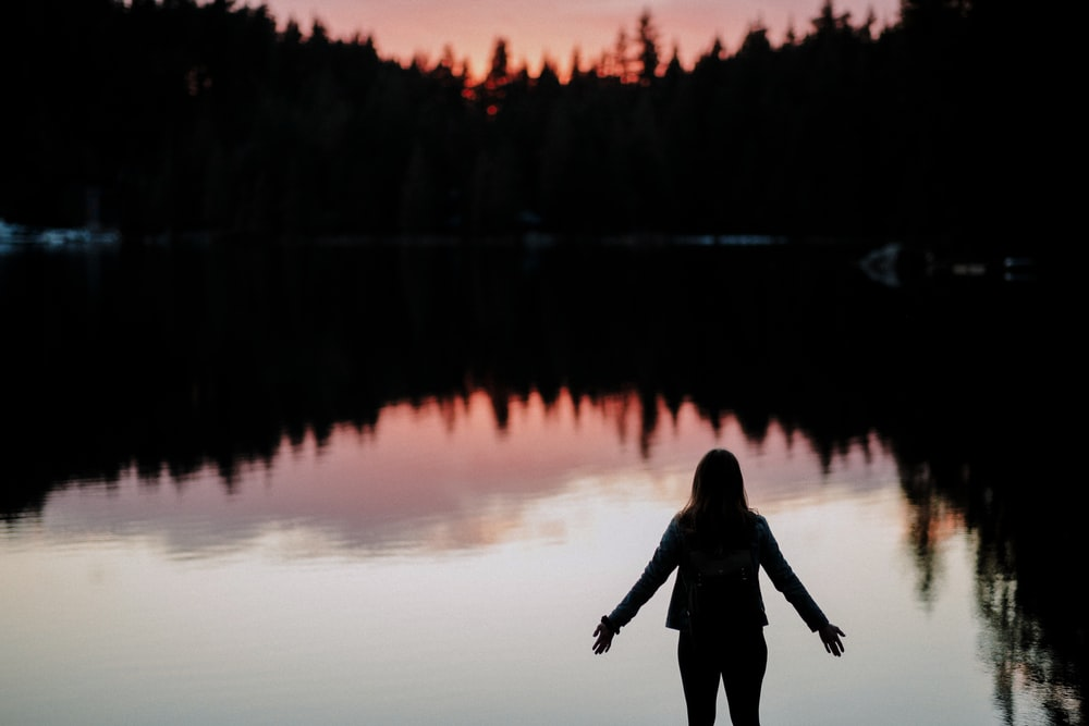 silhouette of person standing beside body of water