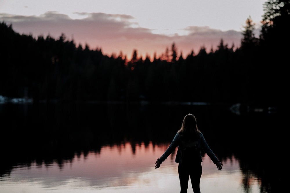 woman standing with hands spread on side facing lake at sundown