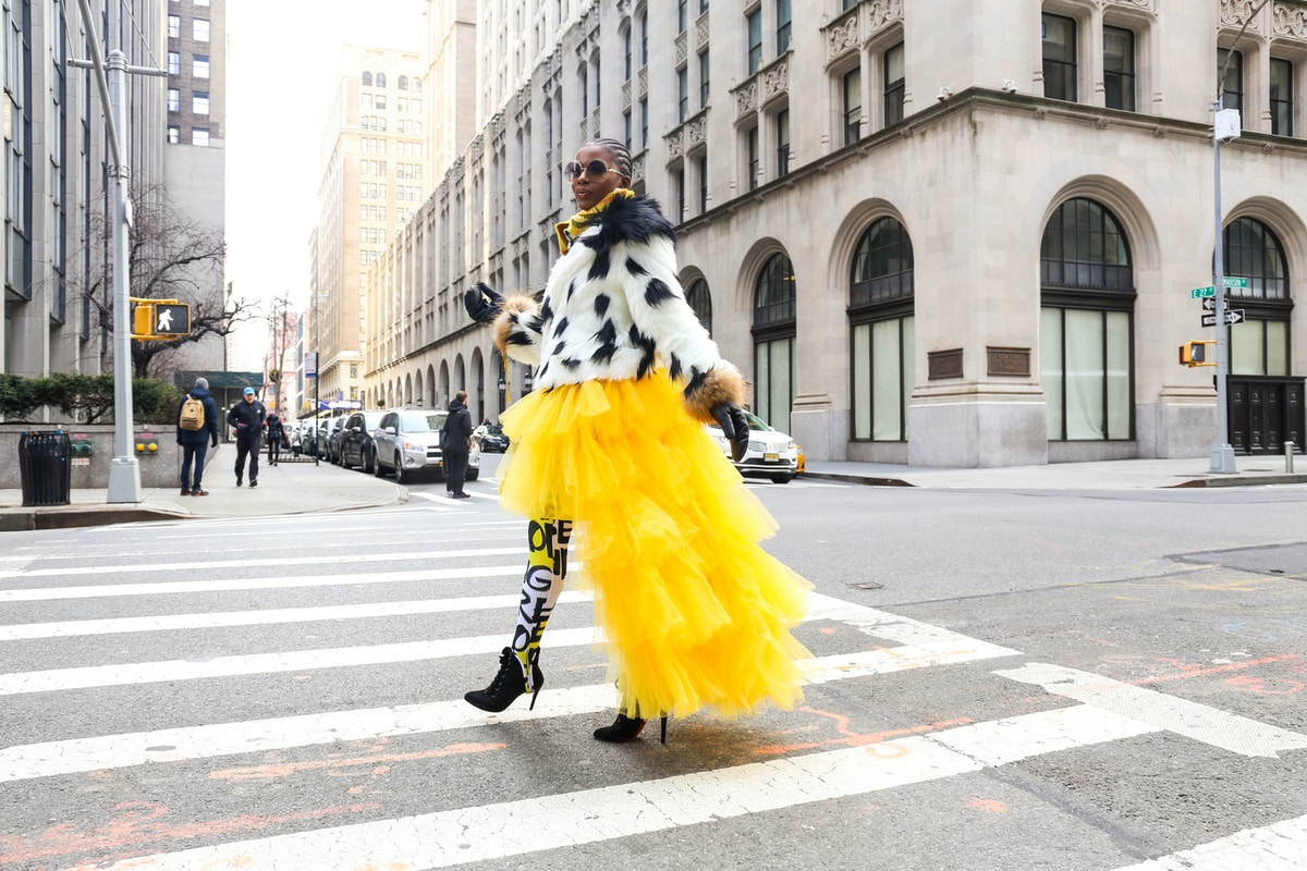 beautiful black woman with cornrows crossing a downtown city intersection wearing bold black and white clothes and a bright yellow tulle skirt