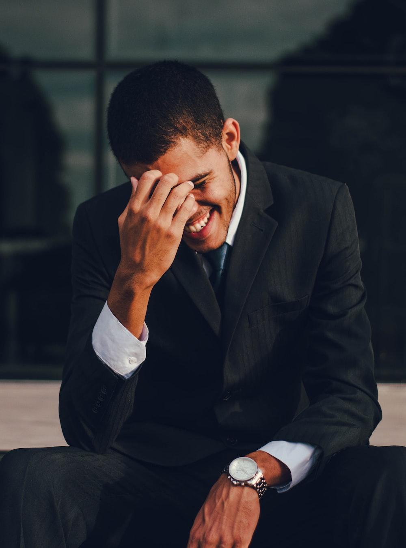man in black suit jacket smiling