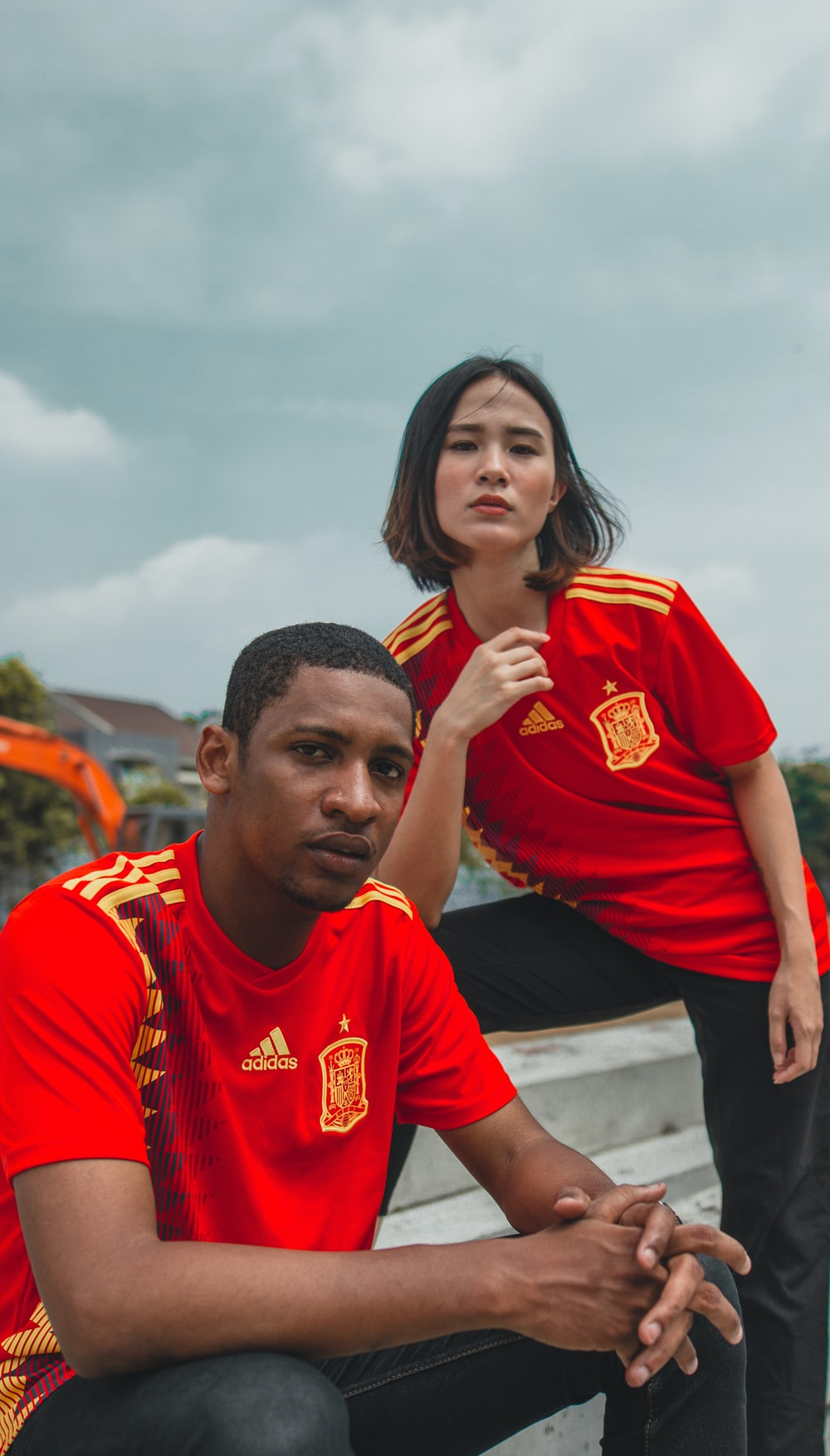 woman wearing red and yellow shirt beside man wearing red and yellow adidas shirts